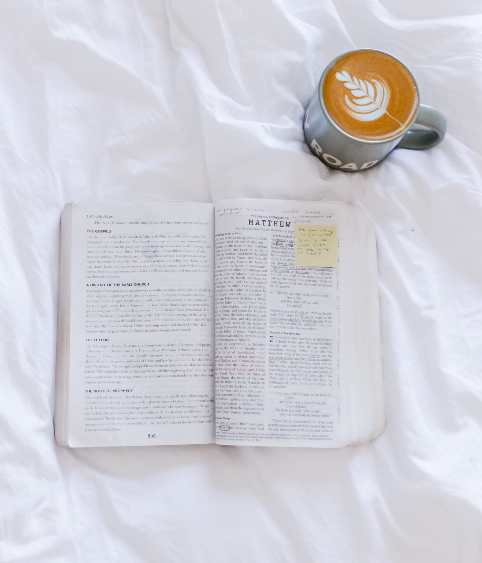 coffe cup with bible on white sheet